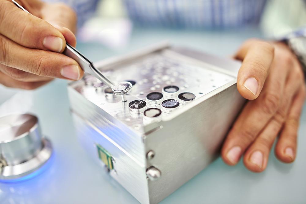 Person inserting a sample in the Phenom XL desktop SEM sample holder